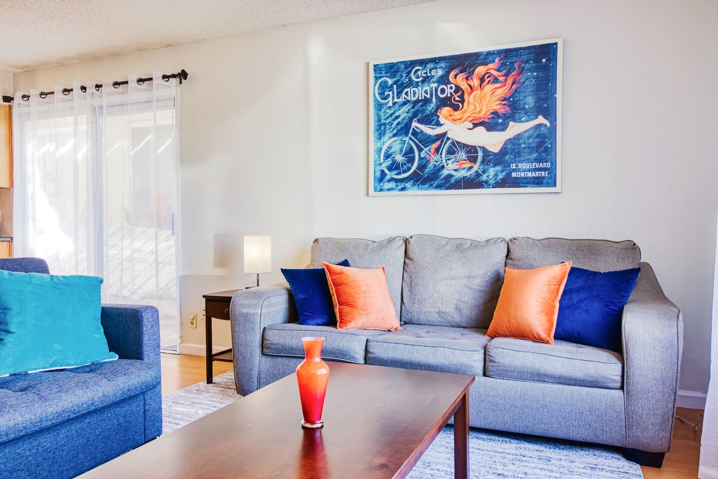 """Living room is large and open with 2 comfortable sleeper sofas, tons of natural light, a 50"""" Smart TV and colorful wall art"""