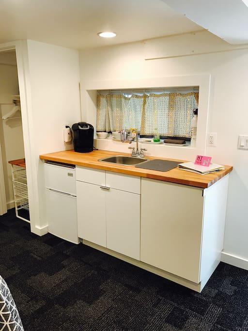 Kitchenette in room with Keurig coffee maker, mini fridge, microwave, glasses, plates, bowls, utensils
