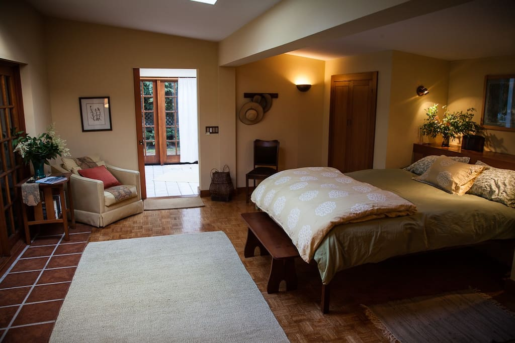 The bedroom is spacious and light with a wall of windows looking to the small garden.