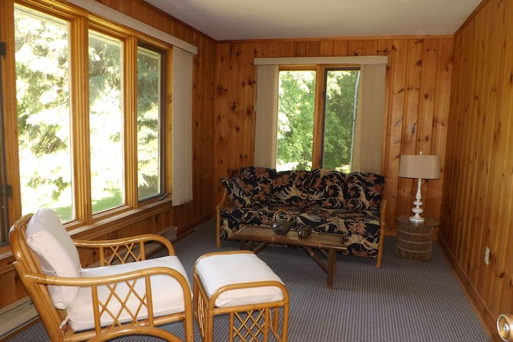 This main floor sun room is a great spot to watch the outdoors.  Open the windows to catch all the breezes.    It can easily be converted to a double bed. The floor is carpeted.