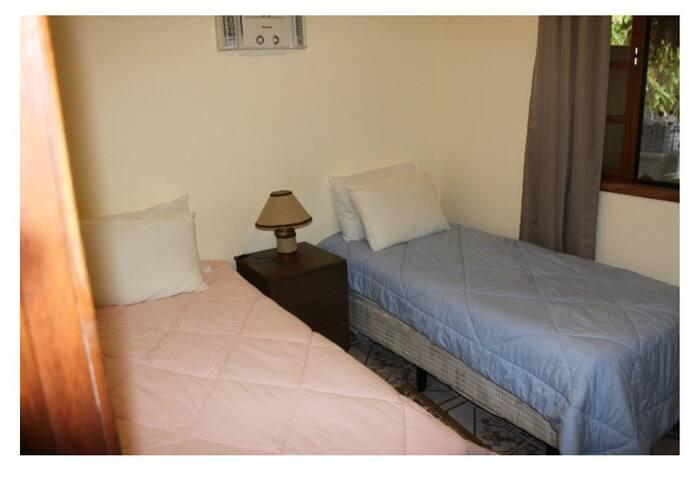 Quarto com duas camas box de solteiro com colchão de molas, ar condicionado e roupas de cama e banho de 100% algodão.