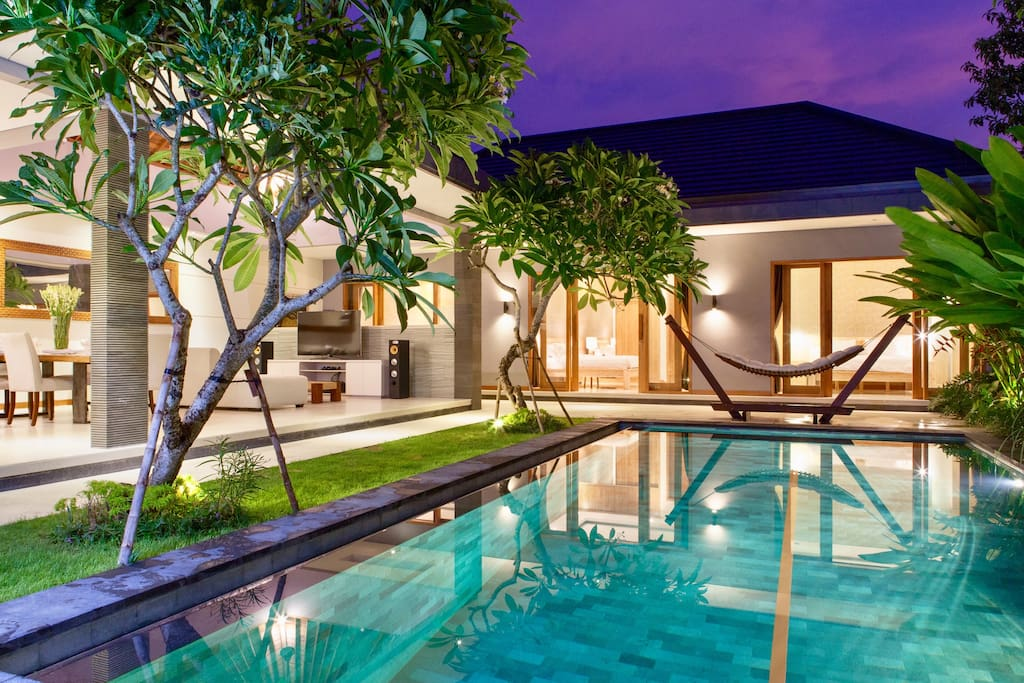 View from pool to the bedrooms and general living area at twilight.