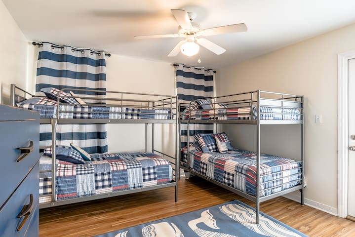 Upstairs room with 4 twin bunk beds. The room has a 32 inch TV and an ensuite bathroom.