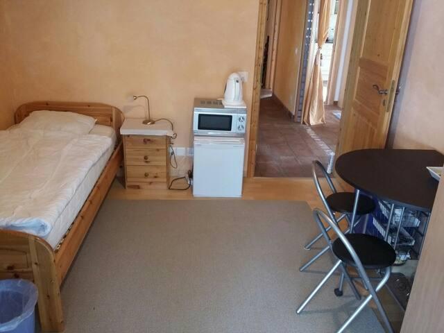chambre avec coin à manger, vaisselle, frigo, micro-onde, chauffe-eau