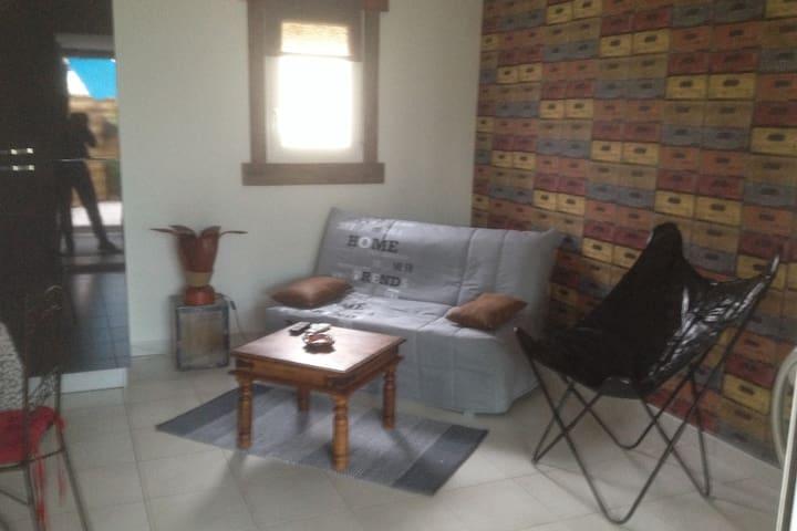 Salon avec Tv séparée de la chambre par une baie vitrée