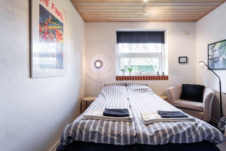 Soveværelse med seng til 2 personer, lænestol, skrivebord og klædeskab.