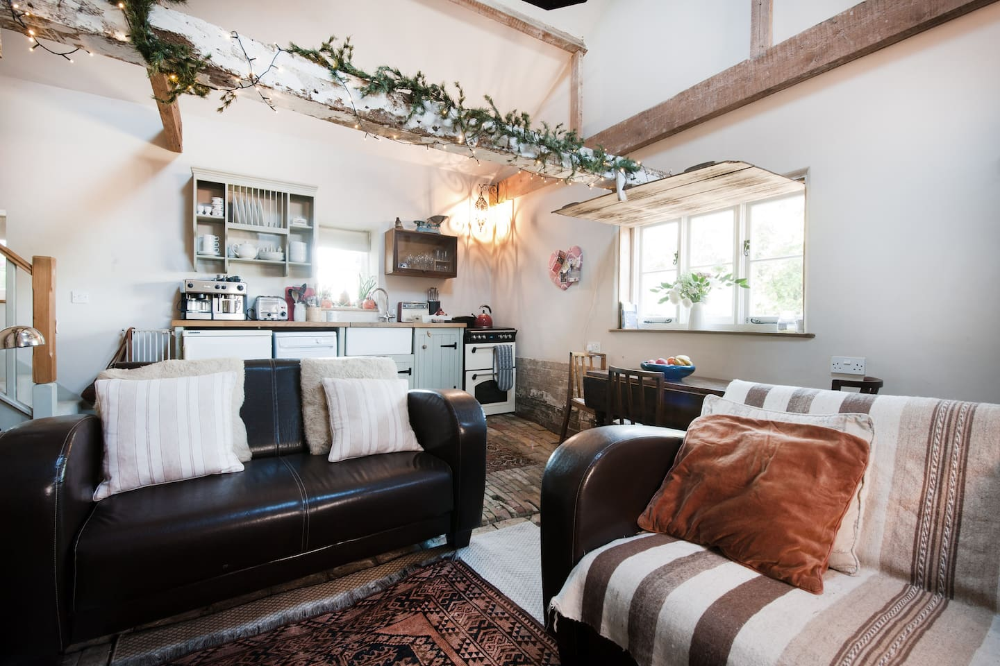 Double height open plan living with original brick floor and wooden shutter