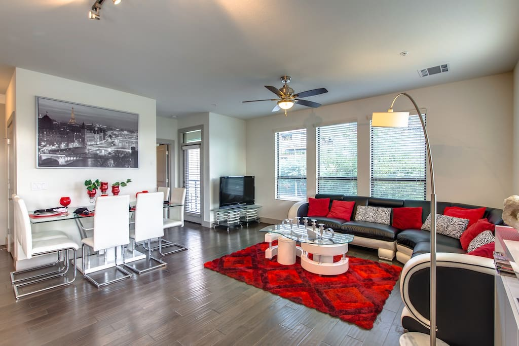 Light and spacious living room with scraped wood flooring,  large windows and access to 2 private patio's.