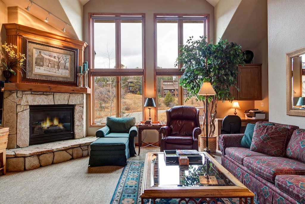 Lots of natural light, comfortable furniture and cozy fireplace highlight the living room