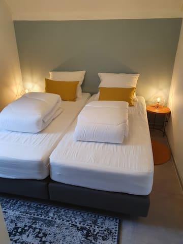 Derde slaapkamer, op de begane vloer, naast de badkamer. Dit bed kan ook als 1 persoons bedden, en als lits jumeaux opgemaakt worden.