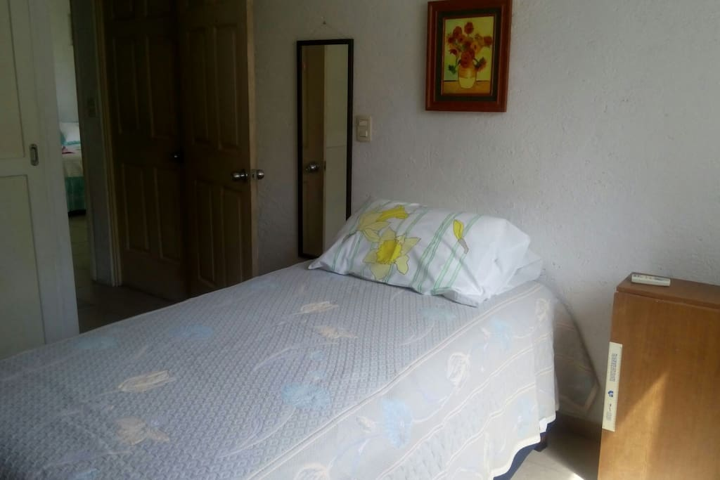 La cama individual con espejo y mesa plegable para trabajo.