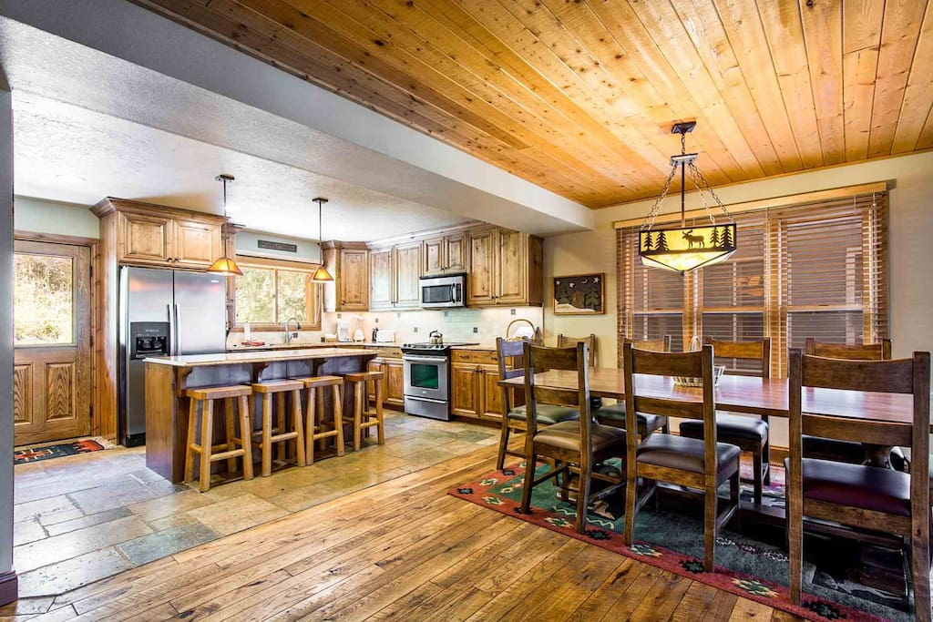 The large family living room has an authentic mountain feel in it's design with cathedral ceilings, antique décor and wood and stone finishes.