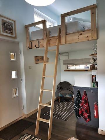 Sleeping mezzanine with ladder in use.