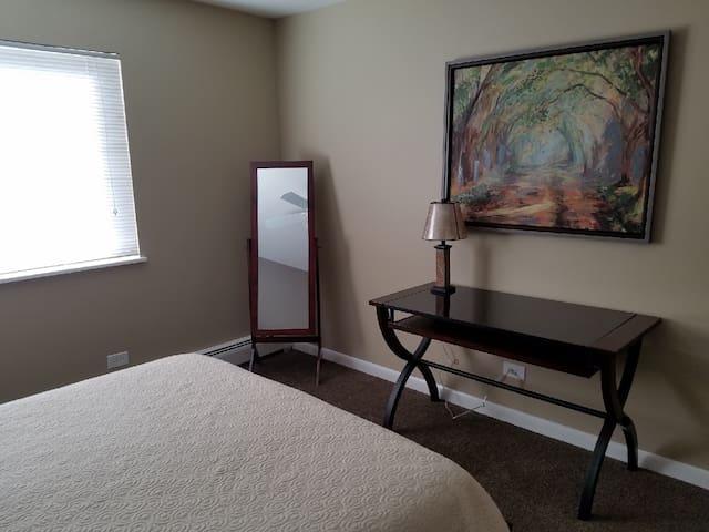 Bedroom with desk and floor mirror
