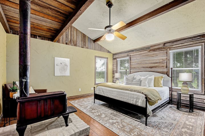 King size iron bed with upholstered headboard, iron nightstands with antiqued mirror tops, and an original oil on canvas painting by local artist Courtney Walker add a sophisticated touch to this country room.