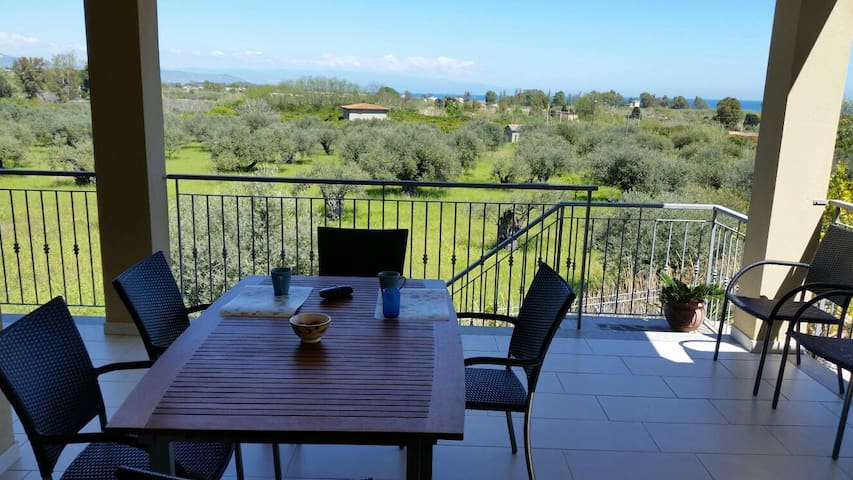 Terrasse with view over olive grove and the sea in one direection and the mountains in another direction