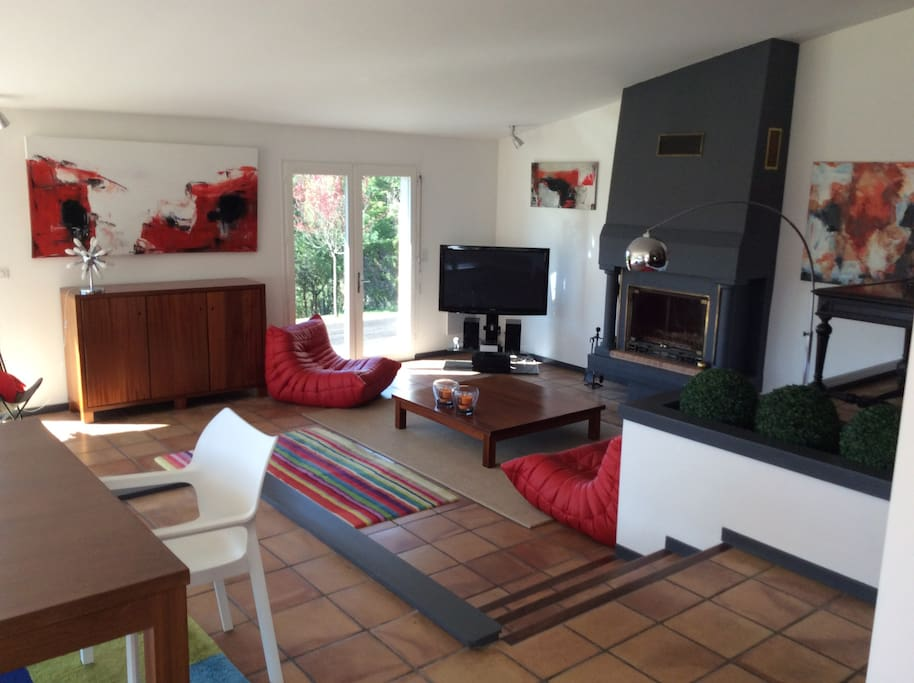 Large living room with fire place opened on the garden and sun light
