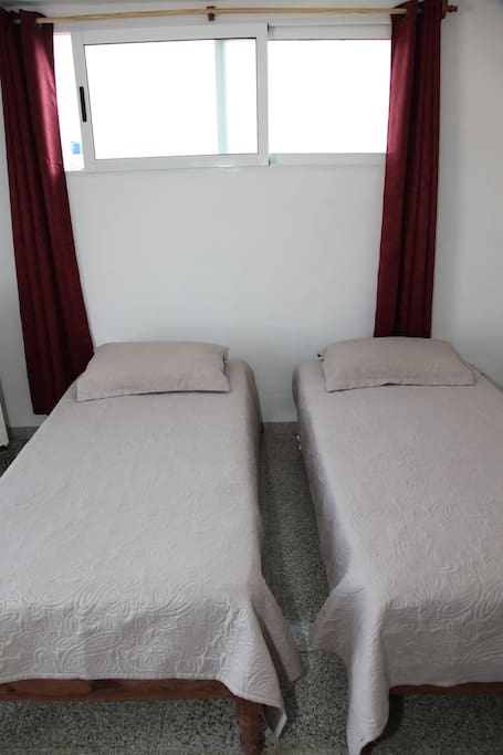 Two single beds in Rooftop Room 1, curtains for privacy