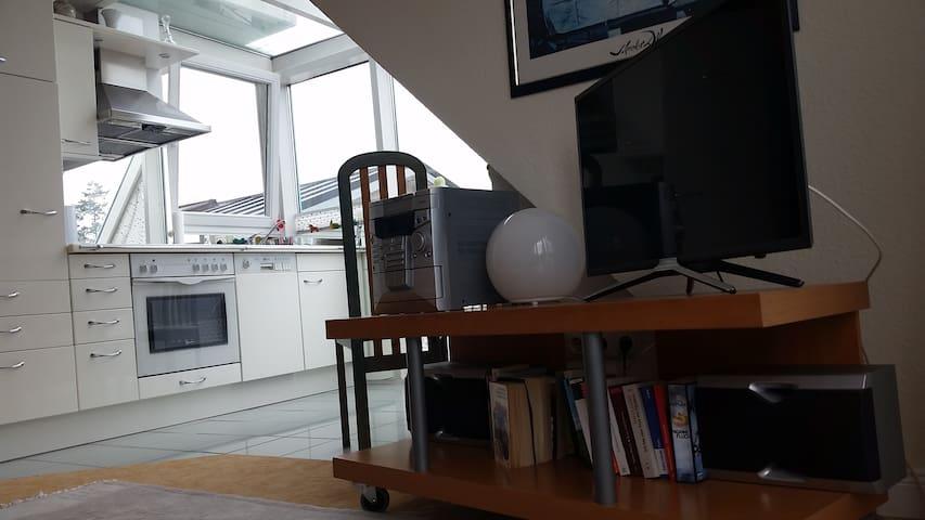 Blick in die offene Wohnküche mit Tisch und Stühlen