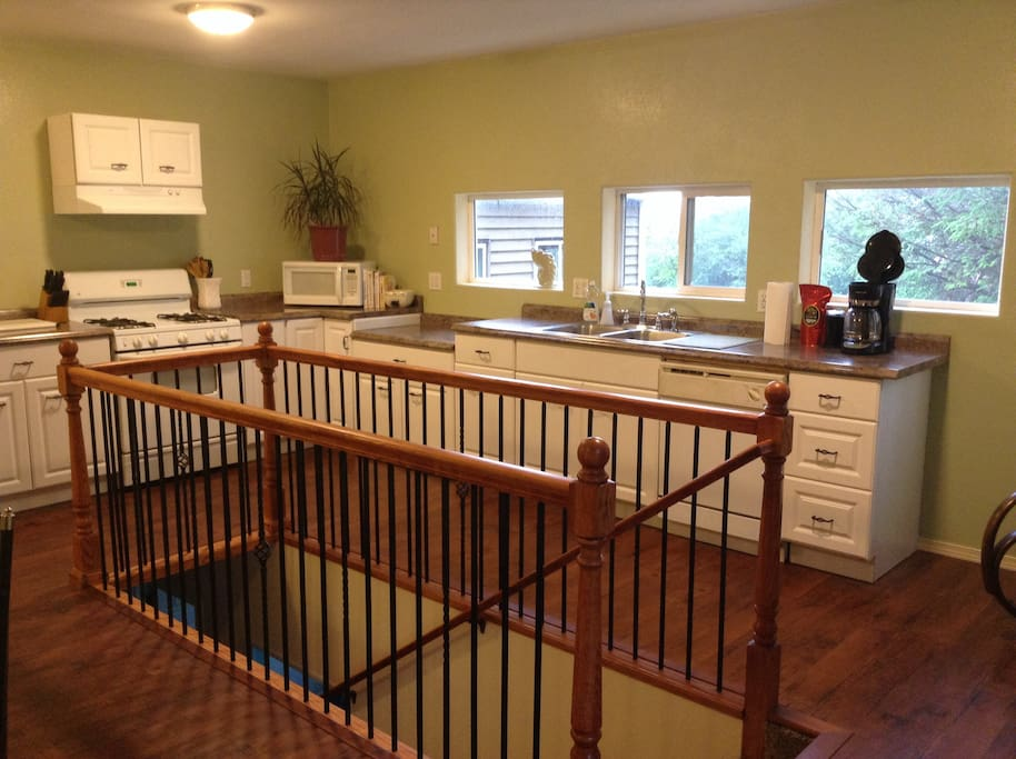 Full kitchen opens to dining area and stairs to lower level.