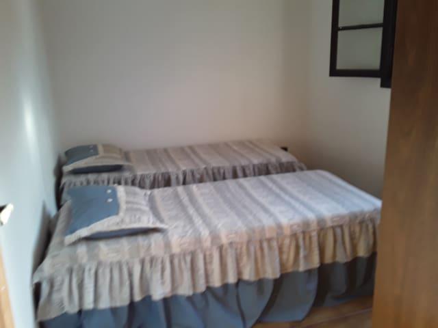 Quarto 2 com duas camas de solteiro e armário três portas.