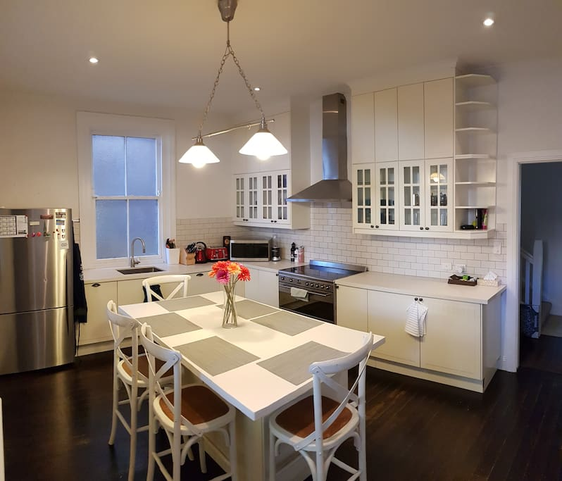 Contemporary eat-in kitchen with stainless steel appliances, ideal for family gathering.