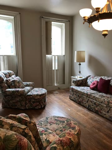 Large parlor gathering space, with windows on South Market Street, comfortable queen sofa bed, and table/chairs in front of fireplace