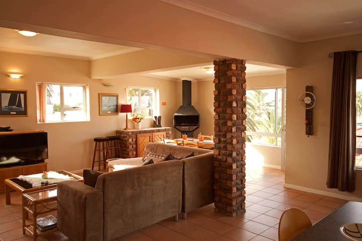 Large open plan lounge, dining, braai and kitchen area. This apartment is very spacious and private, looking over the rooftops is a small view of the sea.