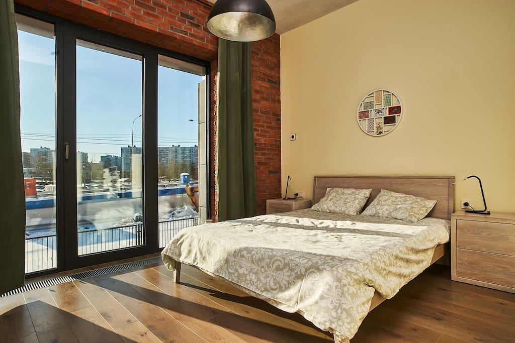 Спальня с большими французскими окнами. Удобной двуспальной кроватью и телевизором.