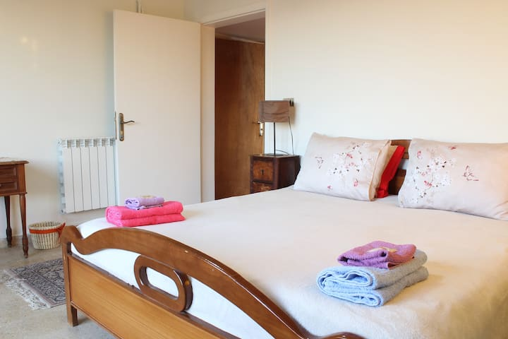 A double bed room with a window to the west and a door to a private balcony to the north