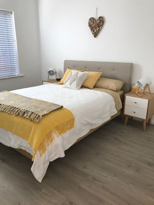 Sunny spacious bedroom with a queen size bed.
