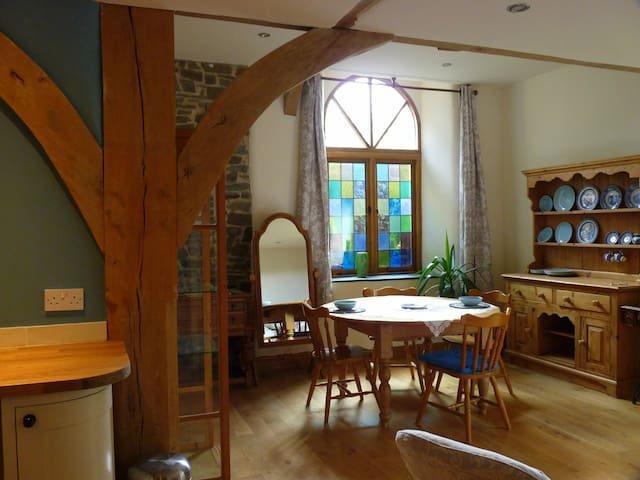 Open plan living area looking towards the chapel window with coloured leaded lights.