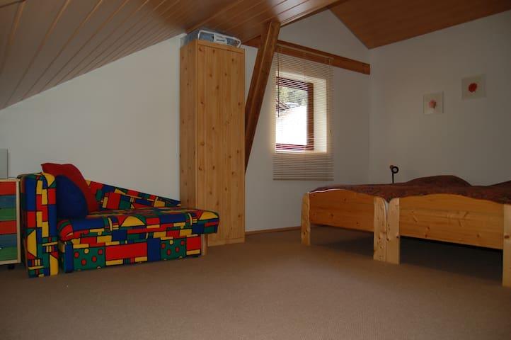 Een grote zolderslaapkamer met 2 singel bedden plus extra bed, dat is ingeklapt. Er is ook een kinderbedje (groen/geel/rood/blauw) en een campingbedje voor een baby