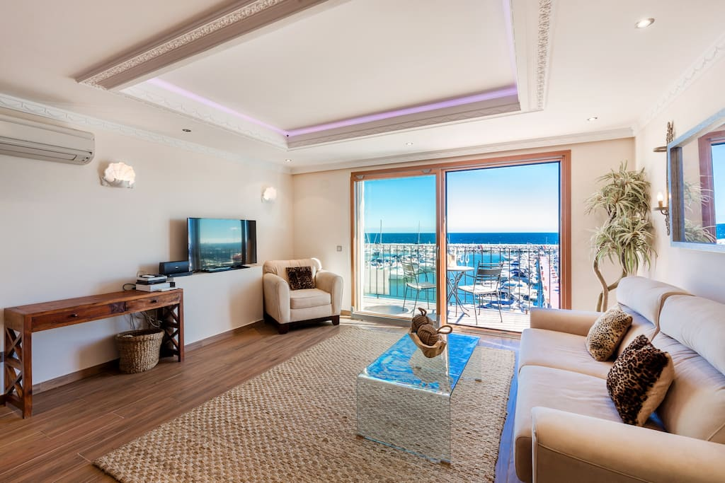 Nice living and dining room with plush sofa and great views in Puerto Banus, Marbella.Living room with flat screen TV and high speed fiber optics internet