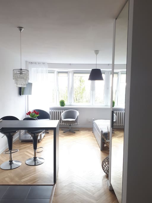 Widny, przestronny pokój dzienny,  fotele,  stolik, mapki Warszawy oraz informatory kulturalno -rozrywkowe.