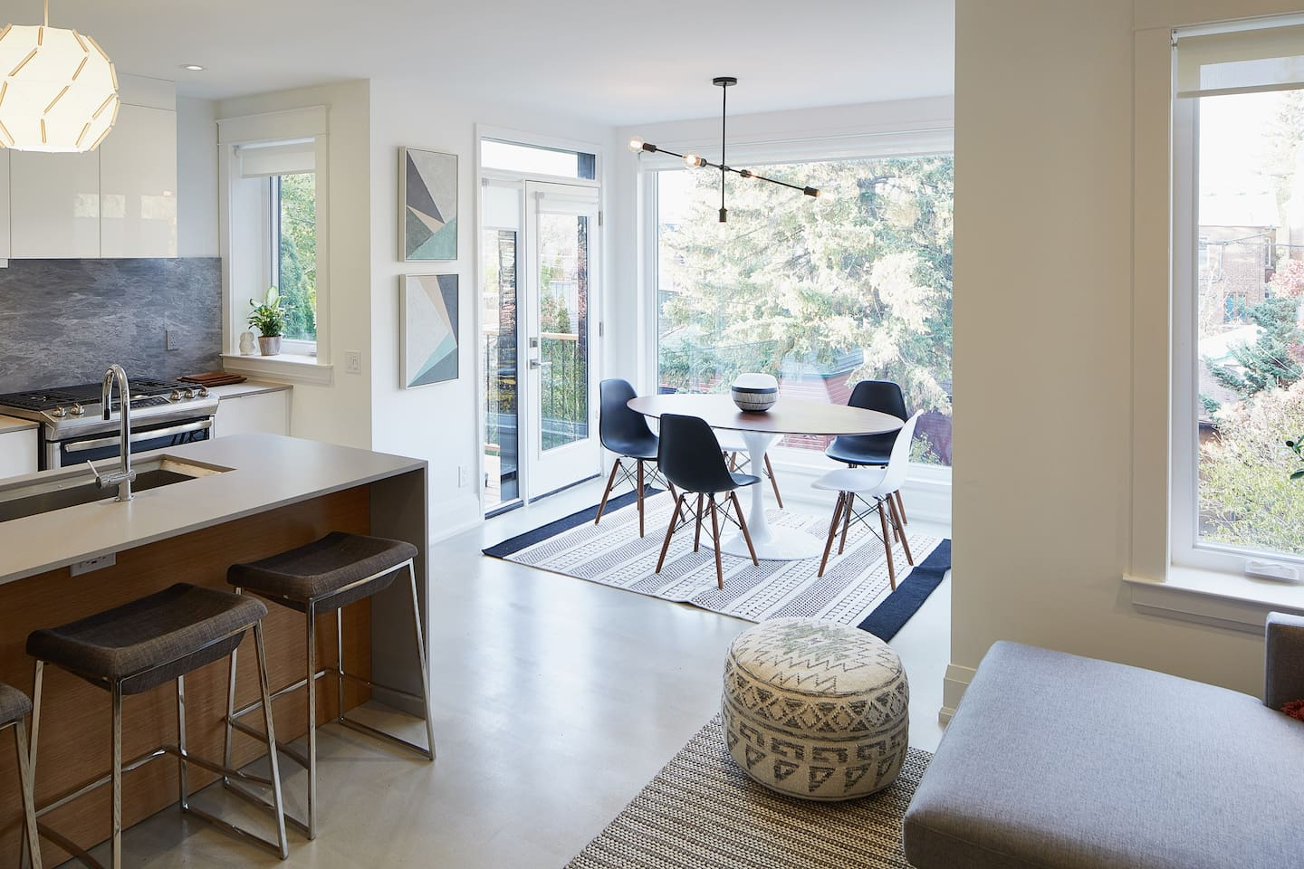 Floor-to-ceiling windows allow natural light to fill the dining room, living room and kitchen.