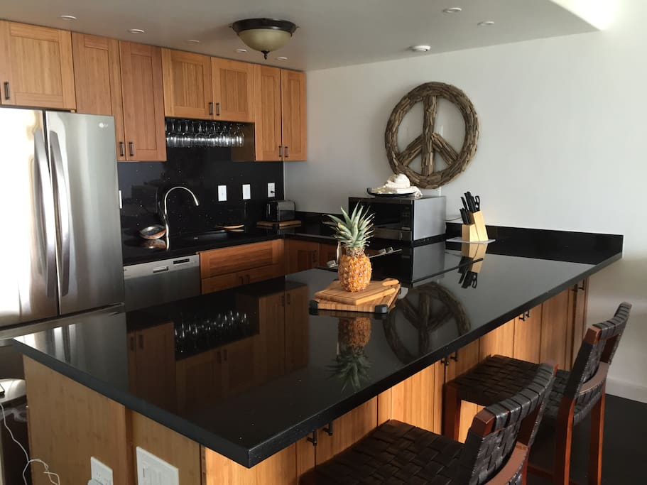 Kitchen with seating around a huge black granite island