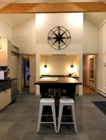 The spacious kitchen has beautiful cathedral ceilings, all new appliances, soapstone counters and cool slate floors.