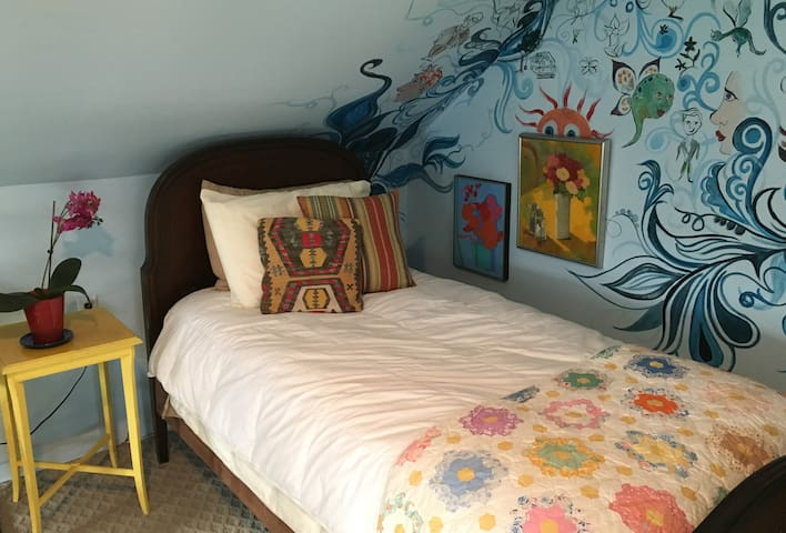 Twin bed with memory foam topper in 2nd bedroom with original film location artwork.