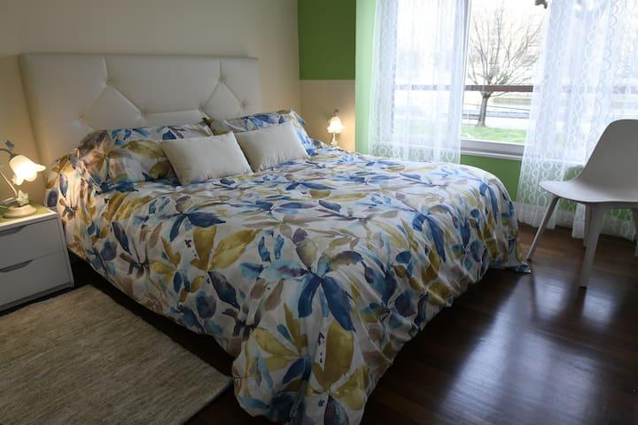 Dormitorio exterior con cama de matrimonio