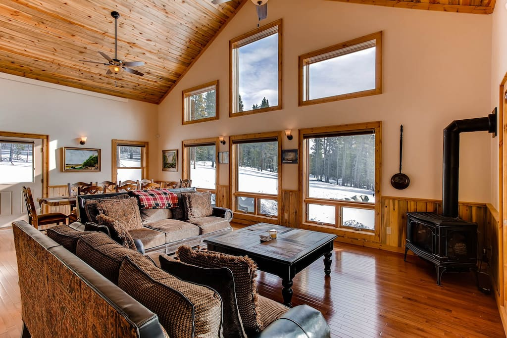 The living room has floor to ceiling picture windows and a cozy gas stove.