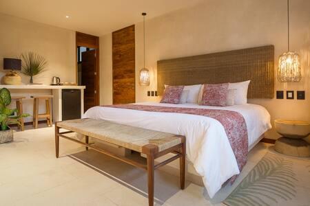 Habitación con cama king size, acceso a cuarto de baño completo y zona con frigo bar.