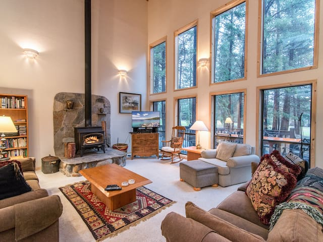 The welcoming living area boasts large windows, a wood-burning fireplace, and high-vaulted ceilings.