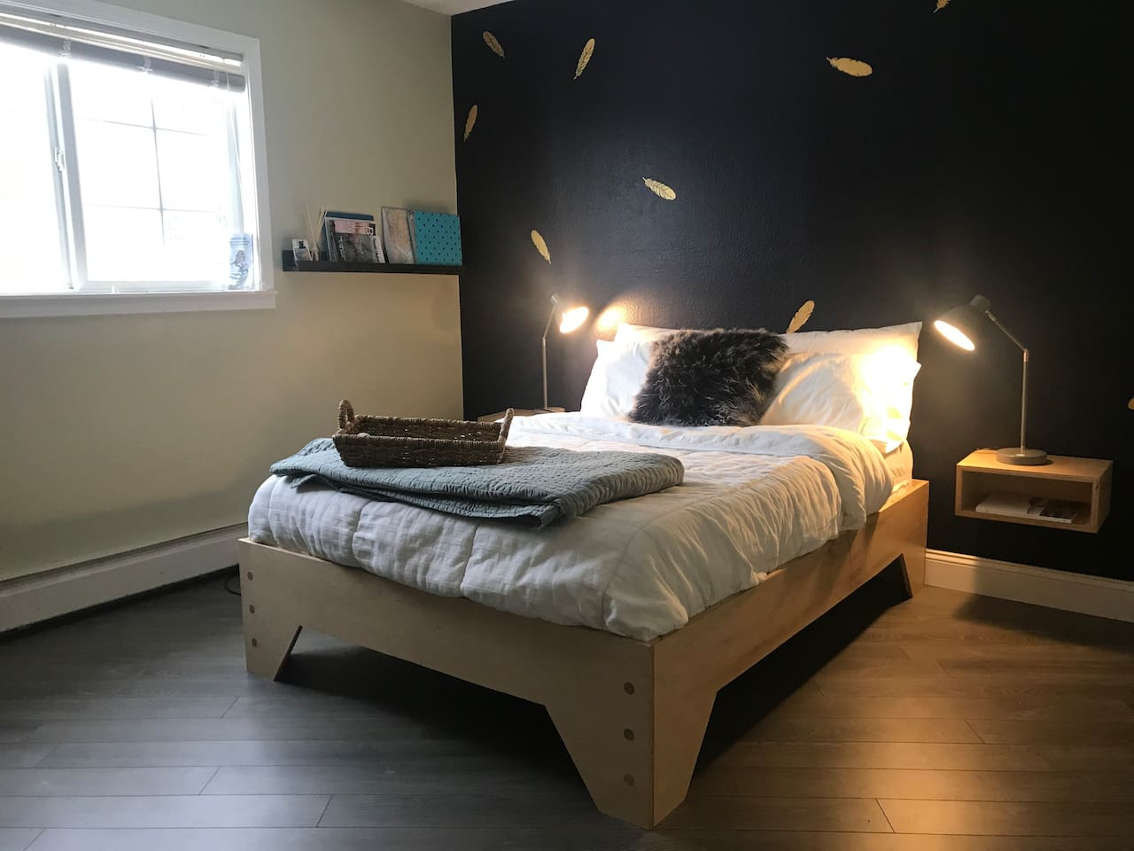 Enjoy a quiet night's rest on this hand-built bed with touch lights and a wooded backyard view.