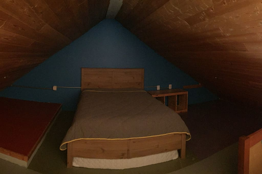 Queen sized bed in the loft area of the main house