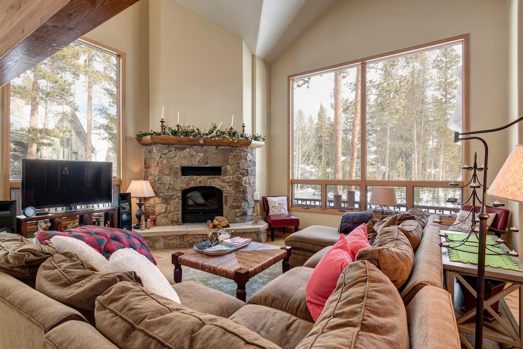 Main floor family room with woodburning fireplace, huge couch, big windows with great views, tv etc all next to dining room table and kitchen for family stays engaged during dinner prep etc.