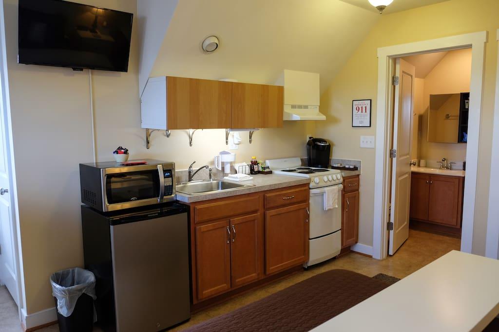 Kitchen with TV, Refrigerator, Microwave, Half-Range, and Single-Serve Keurig