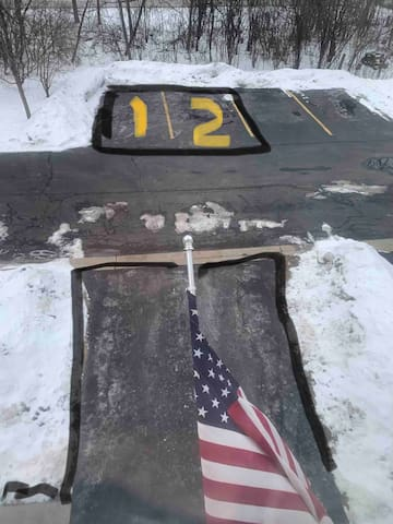This winter view was taken from my master bedroom with a flag over my driveway. Guest parking may include spaces marked 1 or 2, or my driveway. I will do my best to communicate before arrival. Parking in another space may result in a $25 penalty!