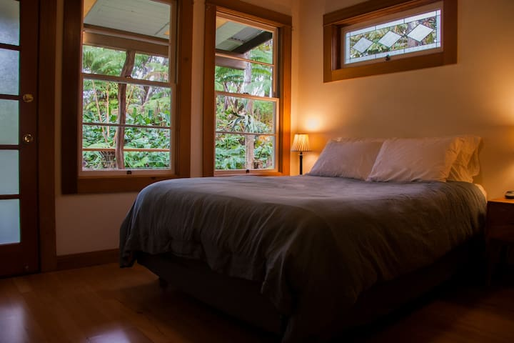 The master bedroom offers a comfy heated queen bed, a tranquil view of the forest, and its own door to the lanai.