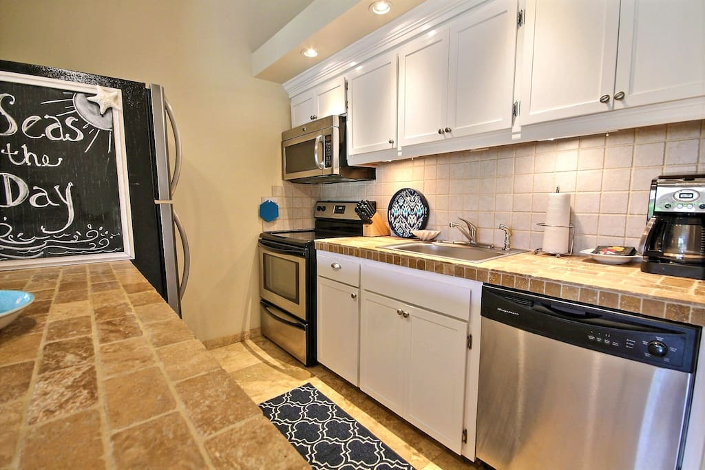 Galley kitchen with full size fridge, stove, dishwasher, and microwave
